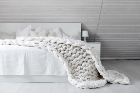 Cozy white scandinavian bedroom interior at cabin, Beautiful merino woolen plaid decorated bed and floor, super chunky yarn knitted blanket, nobody Stock Photo