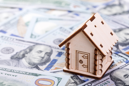 Mortgage concept. Wooden model of house on dollar banknotes background