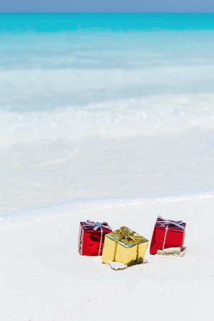 Christmas present box on tropical beach, packed gifts on sand with azur sea background and copy space. Holiday greeting card