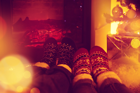 Couple sitting in woolen socks and warming up their feet near fireplace in living room , decorated for Christmas holidays