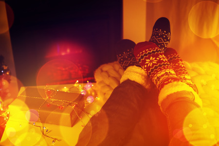 Couple sitting in woolen socks near fireplace in living room decorated for Christmas holidays
