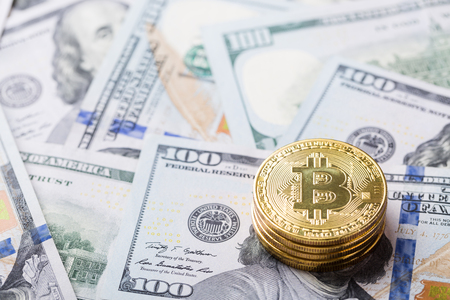 Bitcoins on dollar banknotes background, closeup