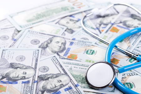 Stethoscope on dollar banknotes background. Paid medicine concept