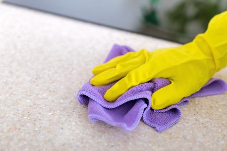 Mains de femme nettoyant le dessus de cuisine en granit dans des gants en caoutchouc, concept d'entretien ménager Banque d'images