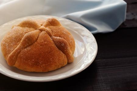 Dia De Los Muertos (Day of the Dead) -  pan de muerto (traditional Mexican bread) on wooden table in plate, selective focus