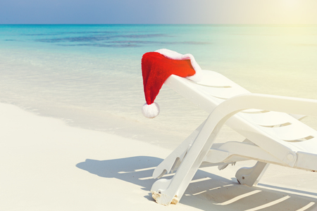 Santa Helper Hat on sun lounger, Christmas greeting card with copy space. White sandy beach and beautiful sea backgound, nobody