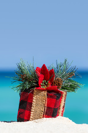 Tropical celebration on beach. Present box on sand against turquoise caribbean sea water Stock Photo