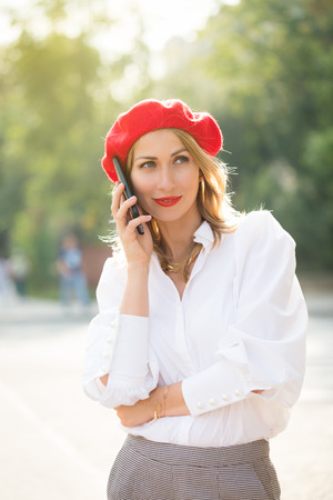 Portrait of beautiful woman wearing red beret and lips, talking on a mobile phone.