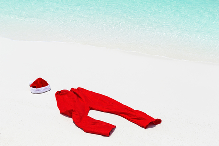 Santa costume lying on sand, close to sea and beach, nobody. Christmas holidays on tropical destinations