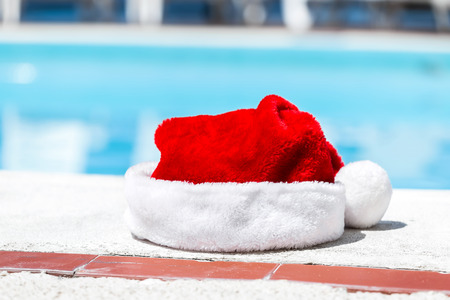 Santa hat near swimming pool with clean turquoise water Stock Photo