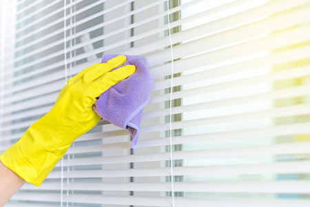 Hand of woman closeup cleaning blinds; housework concept, no face
