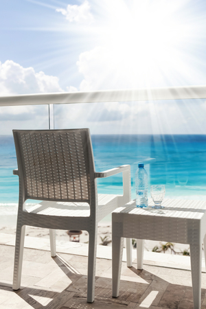 Balcony with plastic bottle of water on wicker table overlooking an ocean