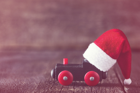 Old toy of train with Santa Claus helper hat on it. Winter holidays celebration