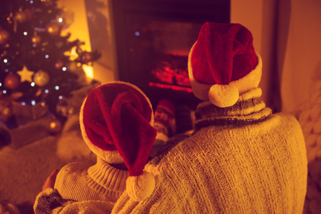 Couple in Santa hats, sitting in woolen socks near fireplace in living room decorated for Christmas holidays, hugging and enjoying life