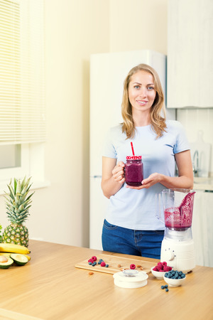 Young caucasian blond woman preparing detox fruits smoothie in blender on white kitchen, healthy eating, cooking, vegetarian food, dieting concept Stock Photo