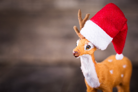 Santa Claus hat on toy of deer over wooden background, nobody