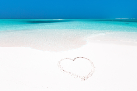 Heart symbol drawing on white sandy beach close to sea, travel concept and romantic card