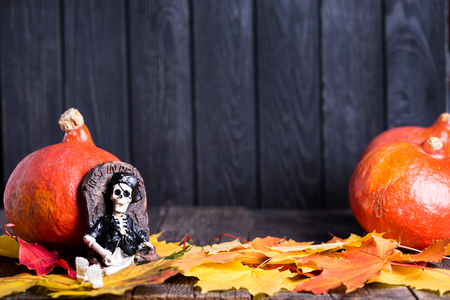 Toy of skeleton with grave, pumpkin and maple leaves on wooden background. Halloween celebration Stock Photo