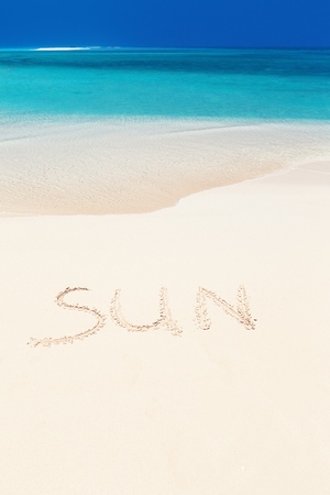 Handwritting inscription word SUN on perfect tropical sandy beach, travel concept card for vacations