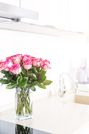 Modern design kitchen interior in minimal style decorated pink roses flowers in vase Stock Photo