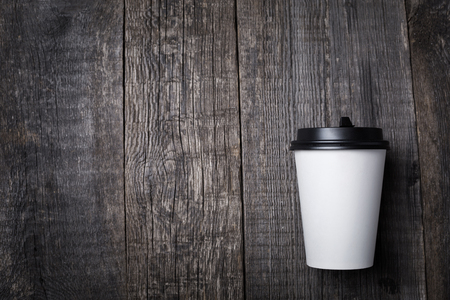 Take away coffee in paper cup on wooden background, closeup