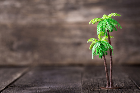 Small toy of palm tree on wooden background, travel concept