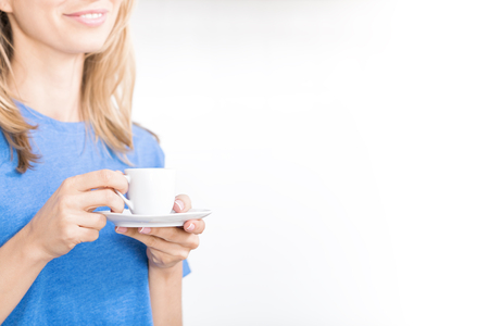 Young caucasian smiling woman drinking coffee on white background, cup of hot espresso in hands with copy space for text, no face