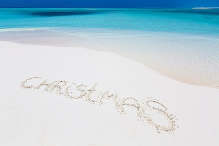 Handwritting inscription word CHRISTMAS on perfect tropical sandy beach, travel vacation concept card for winter holidays Stock Photo
