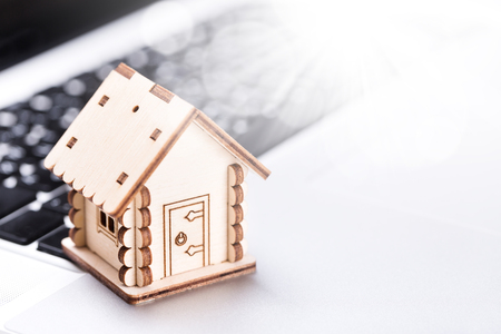 Real estate and property concept. Wooden model of house on laptop keyboard