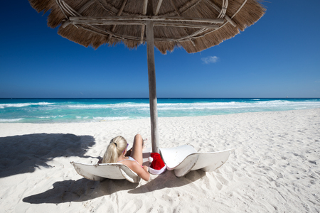 Woman on wooden lounge chairs under sun umbrella celebrating New Year on tropical shore. Beach christmas vacations