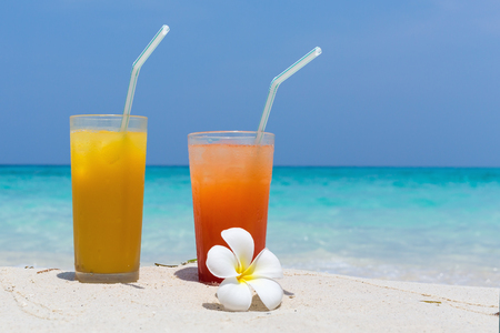 Two Cocktails in glass on white sandy beach decorated plumeria blossom with sea background. Travel card with copy space, nobody Stock Photo
