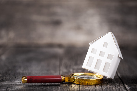 Real estate and property concept. Magnifying lens and model of house on wooden background Stock Photo