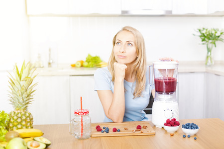 Young caucasian blond woman preparing detox berries smoothie in blender on white kitchen, healthy eating, cooking, vegetarian food, dieting concept