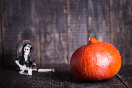 Pumpkin and toy of skeleton with grave on wooden background. Halloween concept