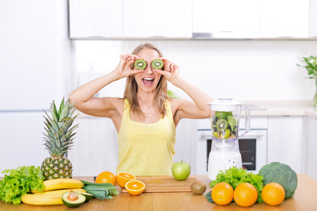 Young caucasian blond woman have fun and preparing detox fruits smoothie in blender on white kitchen, healthy eating, cooking, vegetarian food, dieting concept
