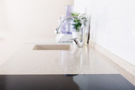 Kitchen background card with focus on countertop and induction top, nobody, mock up, shallow depth