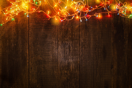 Christmas garland on wooden background. New year lights frame Stock Photo
