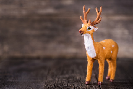 Toy of deer on wooden background, nobody