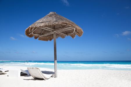 Sun umbrella with wooden lounge chairs on tropical shore. Beach vacations
