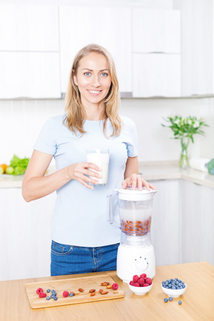 Young caucasian blond woman preparing detox berries smoothie with almond milk in blender on white kitchen, healthy eating, cooking, vegetarian food, dieting concept