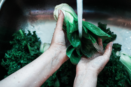 Woman washing in water in sink green chok poy leaves in kitchen, organic healthy food, dark mood image