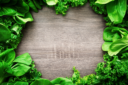 Chok poy and Kale leaves salad frame background board with copy space, healthy eating, organic vegan food concept card