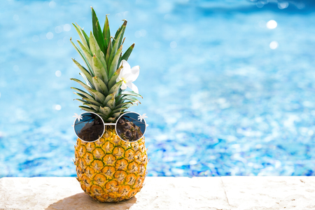 Funny happy pineapple in sunglasses on swimming pool background at tropical sunny day. Creative food and travel concept card with hipster ananas in glasses