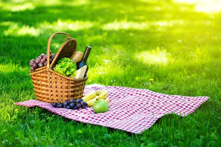 Rieten picknickmand met kaas en wijn op rood geruit tafelkleed op groen gras buiten in zomerpark, geen mensen