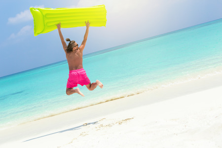 Man with inflatable color green mattress jumping on tropical beach close to sea, enjoying life and having fun on summer vacations 写真素材