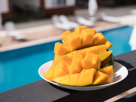 Half cutted cubes slices ripe mango on balcony rail with poolside background, nobody