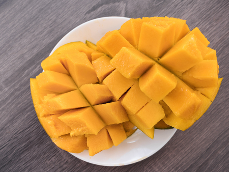 Half cutted cubes slices ripe mango on white plate, top view on table