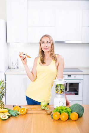 Young caucasian blond sportive woman choosing between healthy food or slice of pizza, fruits for smoothie in blender on white kitchen, clean eating, cooking, vegetarian food, dieting concept