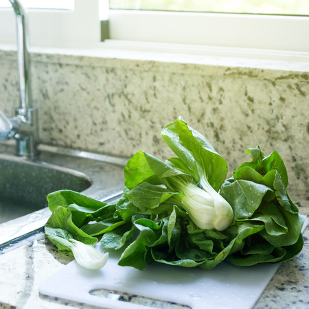 Freshly washed green bok choy leaves in kitchen, organic healthy food Stock Photo