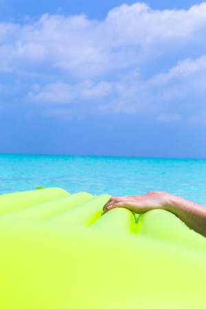 Part of inflatable color green mattress on turquoise sea background, enjoying summer vacations